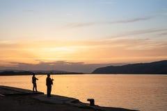 Fiskare som fiskar på kajen av Veliko Gradiste på solnedgången på Danubet River Arkivfoton