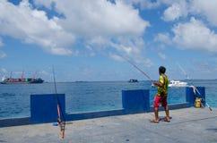 Fiskare som fångar fisken genom att använda tre stänger Arkivfoto