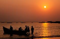 Fiskare som går till att fiska på ett fartyg i havet på solnedgången, Goa, Indien Royaltyfri Foto