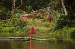 Fiskare som kastar fisknät på sjön Royaltyfri Bild