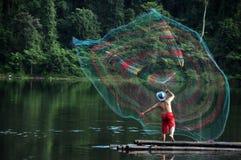 Fiskare som kastar fisknät på sjön Arkivbild