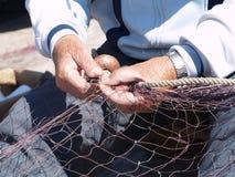 Fiskare som reparerar fisknät Arkivfoto