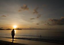 Fiskare som seaching för skal på stranden under soluppgång Royaltyfri Bild