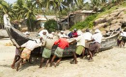 Fiskare som skjuter fiskebåten på stranden Arkivbild