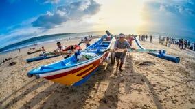 Fiskare som tillsammans skjuter fiskebåten på Jimbaran Bali royaltyfri bild