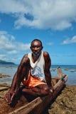 fiskare som vilar på hans utriggarekanot på den bedöva kusten av det tropiska South Pacific havet royaltyfri foto