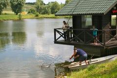 Fiskare tar ut fisken från vattnet Fotografering för Bildbyråer