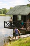 Fiskare tar ut fisken från vattnet Arkivbild