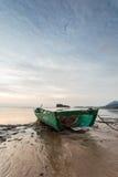 Fiskarefartyg på stranden under dramatisk solnedgång Royaltyfri Bild