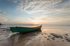 Fiskarefartyg på stranden under dramatisk solnedgång Royaltyfria Bilder