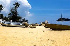 Fiskarefartyget strandade på den öde sandiga stranden under bakgrund för ljus solig dag och för blå himmel Royaltyfri Bild