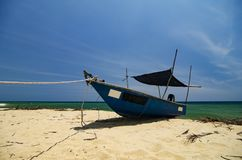 fiskarefartyget strandade på den öde sandiga stranden under ljus solig dag Arkivbilder