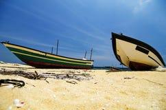 fiskarefartyget strandade på den öde sandiga stranden under ljus solig dag Arkivfoton