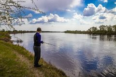 Fiskarefiskar som rotera p? flodbanken royaltyfria bilder