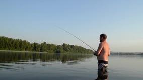 Fiskarefiske i en lugna flod i morgonen Man i fiskekugghjulet som stending i en flod och kast en fiskepol stock video