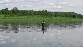 Fiskarefiske i en lugna flod i morgonen Man i fiskekugghjulet som stending i en flod stock video