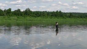 Fiskarefiske i en lugna flod i morgonen Man i fiskekugghjulet som stending i en flod lager videofilmer