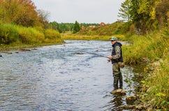 Fiskarefiske på en liten flod royaltyfria bilder