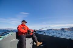 Fiskarefiske på idrottsman nensnurr med havsfartyg Arkivfoto