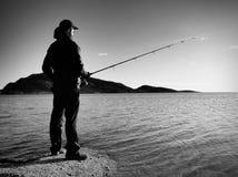 Fiskarekontrollreven och driftigt bete på stången, förbereder sig och kastar drag långt in i fridsamt vatten Arkivfoto