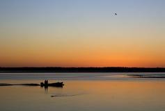 Fiskarekontur på den orange solnedgången med fåglar Arkivfoton