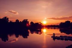 Fiskarekontur på solnedgångbakgrund Vänfishers tycker om att fiska på flodpir Royaltyfria Foton