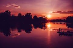 Fiskarekontur på solnedgångbakgrund Vänfishers tycker om att fiska på flodpir pittoresk liggande Arkivbilder