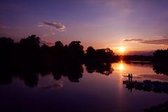 Fiskarekontur på solnedgångbakgrund Vänfishers tycker om att fiska på flodskeppsdocka Royaltyfri Fotografi