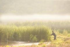 Fiskaren fångar en fisk i dammet royaltyfri fotografi
