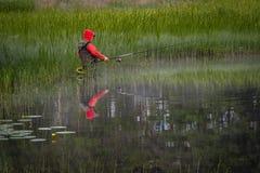Fiskaren fiskar i sjön arkivfoto