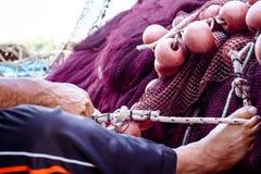 Fiskaren fixar handtaget för fisken netto med hans fot Arkivbild