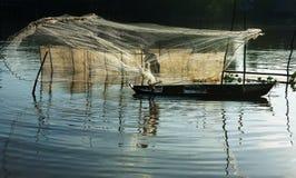 Fiskaren gjuter ett netto på floden Arkivbilder