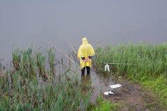 Fiskaren i regnet arkivbild