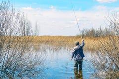Fiskaren med metspöet står i vattnet royaltyfri bild