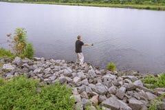 Fiskaren med snurrlås fiskar på floden Arkivfoto
