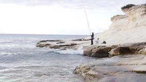 Fiskaren på en vit vaggar låsfisken stock video