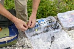 Fiskaren räcker bunden krokfiskeutrustning i ask Fotografering för Bildbyråer