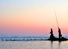 fiskaresilhouettes två Arkivbild