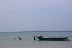 Fiskaresoluppgång sänder och fartyget på stranden Arkivbild