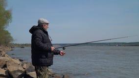 Fiske för hög man på en flod i vår stock video