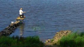 Fiske för hög man på sjöpir som tycker om avslappnande fritid, sommarrekreation stock video