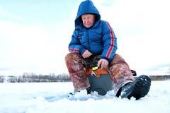 Fiske för vintersäsonggamal man på sjön royaltyfri fotografi