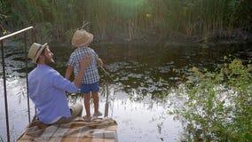 Fiske farsa som undervisar hans son hur man fiskar under familjrekreation på den lilla floden arkivfilmer