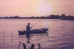 Fiske-fiskare fiske på banken av floden på solnedgången royaltyfri fotografi