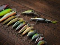 Fiske lockar av olika format på en träbakgrund arkivfoto
