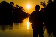 fiske rotering på solnedgången Silhouette av en fiskare Royaltyfria Bilder