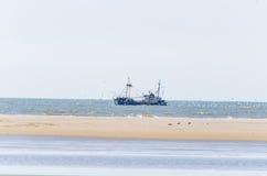 Fiskebåt, fiskmåsar och sand Arkivfoto