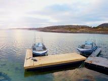 Fiskebåt i fjärdport, solnedgångstillhetvatten En motorbåt för sportfiske Royaltyfria Foton