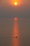 Fiskebåt i havet på solnedgången Royaltyfri Bild