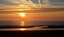 Fiskebåt i solnedgång Arkivfoto